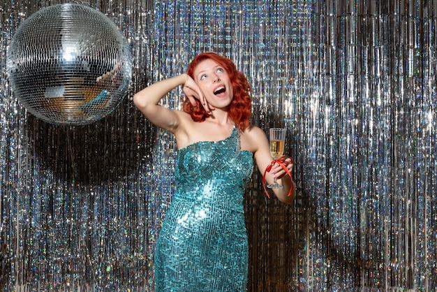 明るいカーテンで美しいドレスを着てパーティーで新年を祝う若い女性