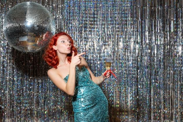 光沢のあるカーテンの上の美しいドレスでパーティーで新年を祝う若い女性