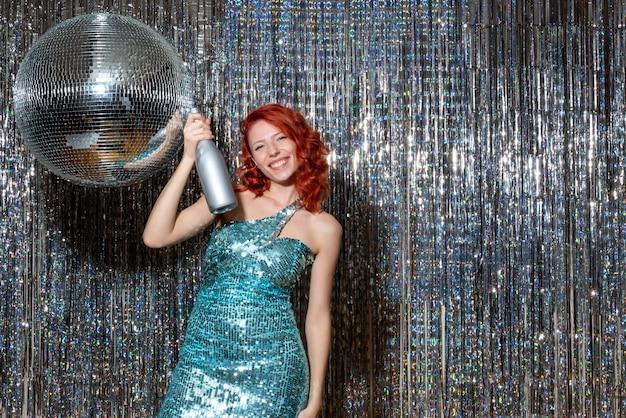 Молодая женщина празднует новый год в вечеринке на блестящих шторах