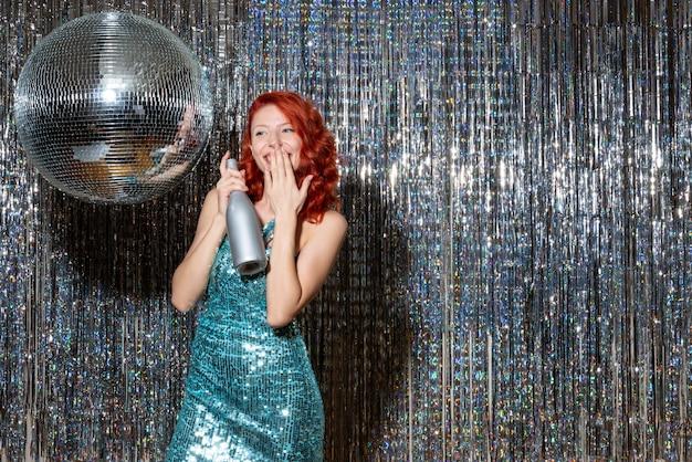 빛나는 커튼에 파티에서 새해를 축하하는 젊은 여성