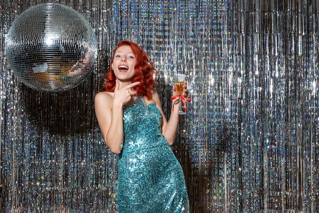 明るいカーテンでディスコボールとパーティーで新年を祝う若い女性