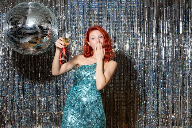 明るい上にディスコボールとパーティーで新年を祝う若い女性