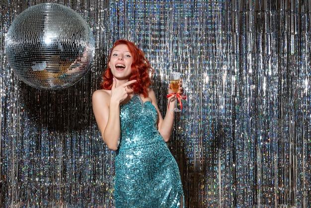 Giovane donna che celebra il nuovo anno in festa con la palla da discoteca su tende luminose