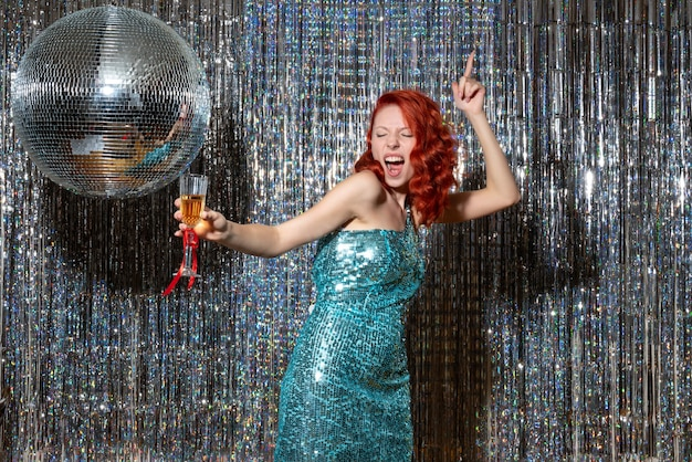 Giovane donna che celebra il nuovo anno in festa con palla da discoteca sul luminoso