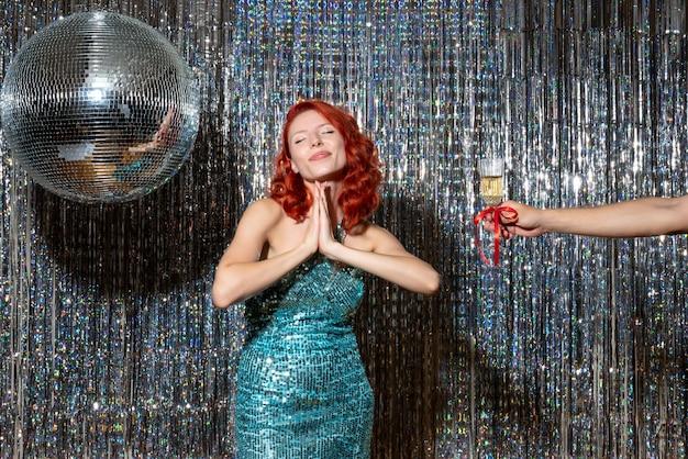 Молодая женщина празднует новый год с мужчиной, предлагая шампанское на блестящих шторах