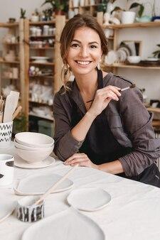 Молодая женщина-керамист в гончарной мастерской.