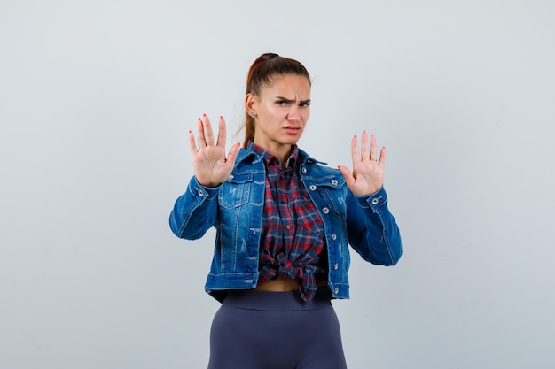 Young female in checkered shirt, jacket, pants showing stop gesture and looking serious , front view.