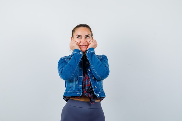 Young female in checkered shirt, jacket, pants with hands on cheeks and looking cute , front view.
