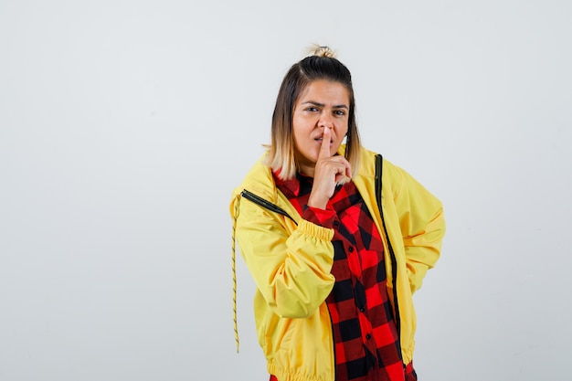 Young female in checkered shirt, jacket showing silence gesture and looking focused , front view.
