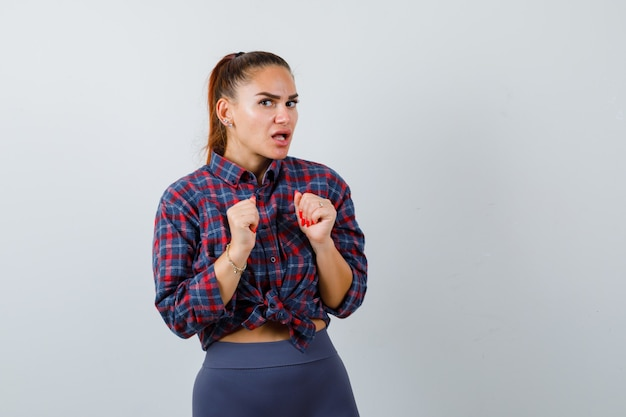 Giovane donna in camicia a scacchi, pantaloni con le mani sul petto e sguardo perplesso, vista frontale.