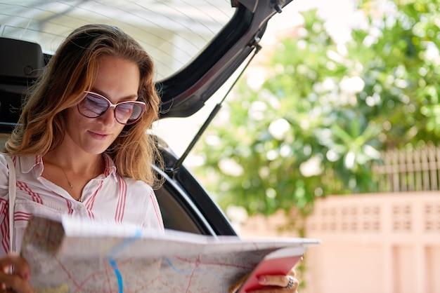 Молодая женщина проверяет карту во время путешествия