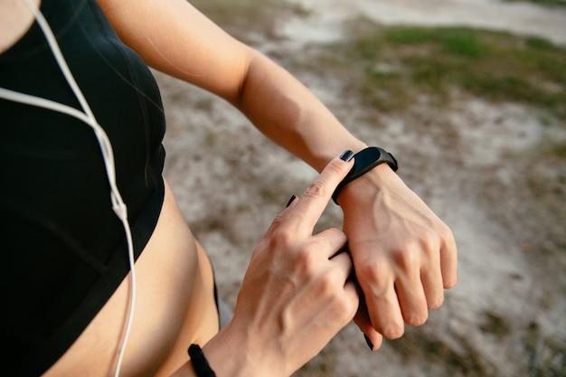 走った後、屋外で、音楽を聴いて、彼女の時計で時間をチェックしている若い女性