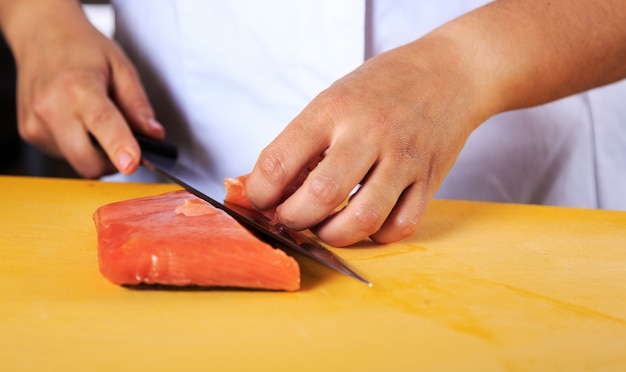 Young female chef coock dressed in white uniform cut salmon fish on the table in restaurant kitchen