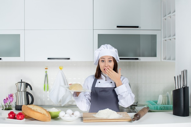 Young female chef in uniform standing behind the table with cutting board foods holding ready meal with surprised facial expression in the white kitchen
