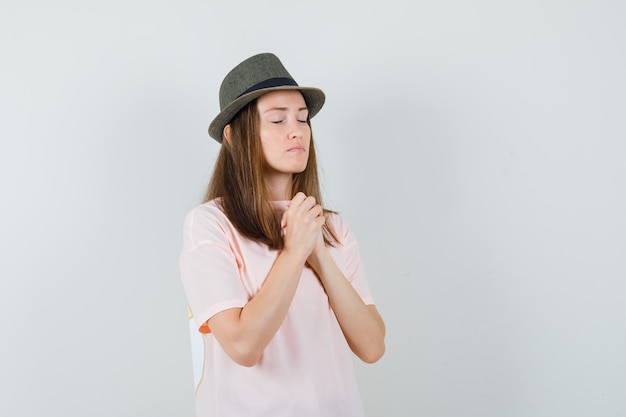 분홍색 티셔츠, 모자에 제스처를기도하고 진정 찾고 젊은 여성 손을 clasping. 전면보기.