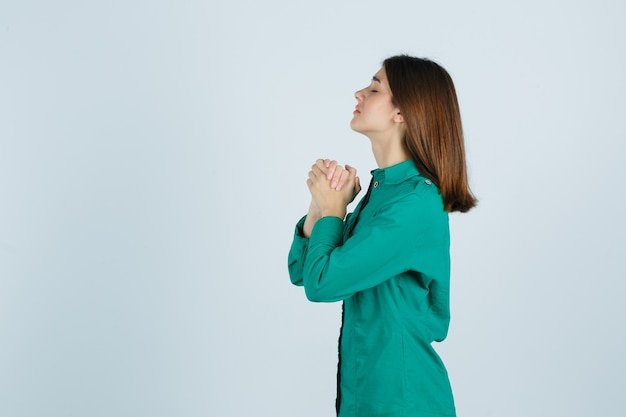 Young female clasping hands in praying gesture in green shirt and looking hopeful. .