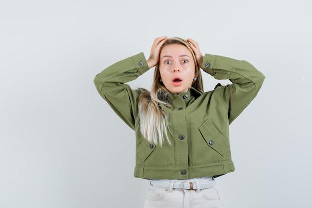 Giovani femmine stringendo la testa con le mani in giacca verde, jeans e guardando spaventato. vista frontale.