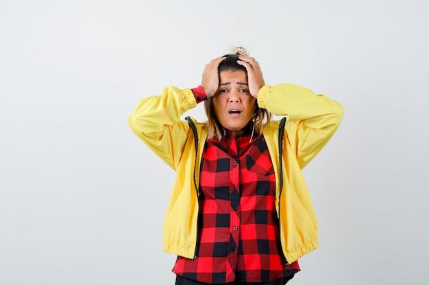 市松模様のシャツ、ジャケット、怖い顔、正面図で手で頭を握り締める若い女性。