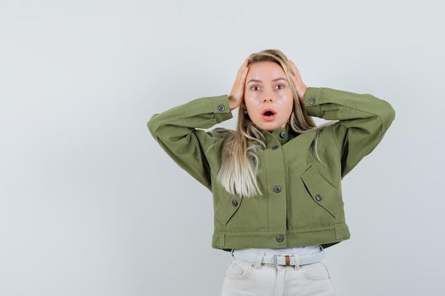 緑のジャケット、ジーンズ、ストレスの多い、正面図で手で頭を握り締める若い女性。