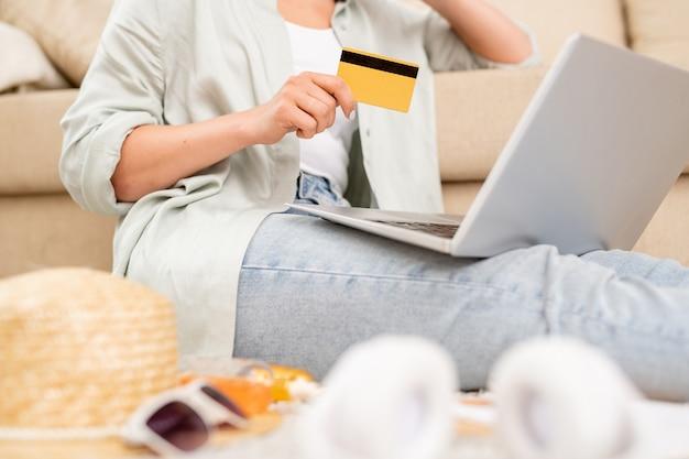 ノートパソコンの前で休暇のためのオンラインツアーを選択するプラスチックカードと旅行会社の若い女性のクライアント