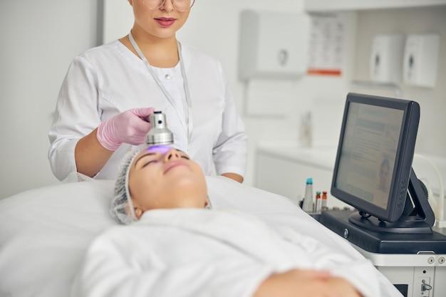 Молодая клиентка с закрытыми глазами, лежа на диване во время косметической процедуры