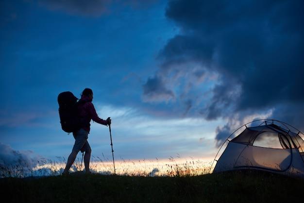 산에서 일몰 지팡이와 관광 배낭에 도달하는 젊은 여성 산악인