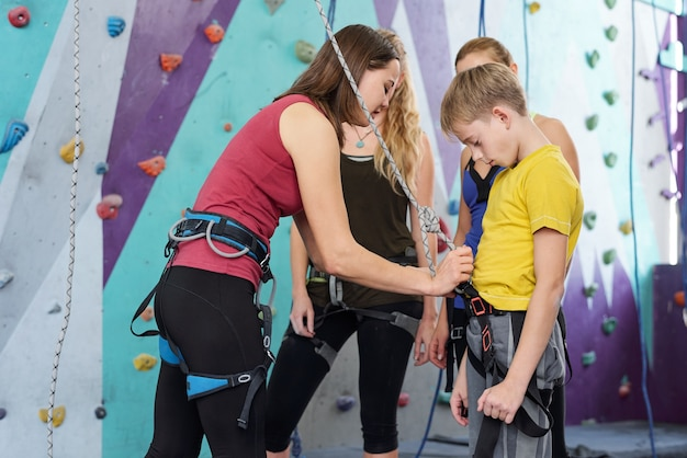 Young female climbing instructor attaching rope to safety belt of youthful boy while showing how to do it properly
