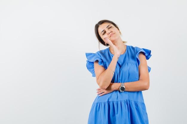 Giovane donna che chiude gli occhi, tiene la mano sulla guancia in abito blu e sembra pensierosa