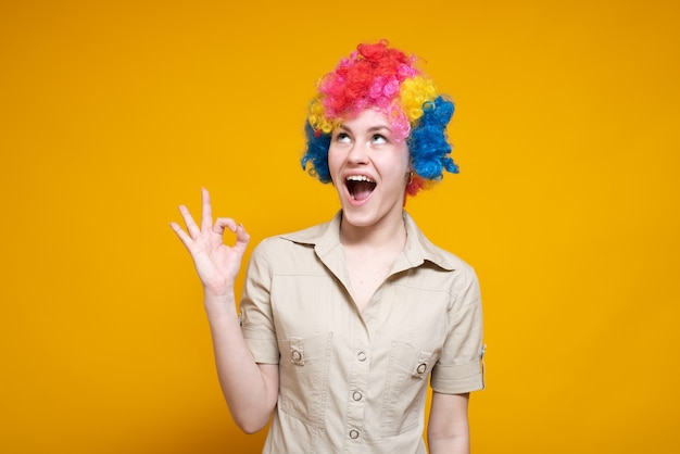 A young female clown shows a gesture ok against a colored background. it's a fool's day.