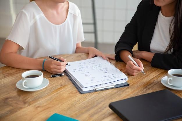 젊은 여성 동료 회의 및 사업 계획 논의, 종이에 전략 계획 작성, 초안 작성