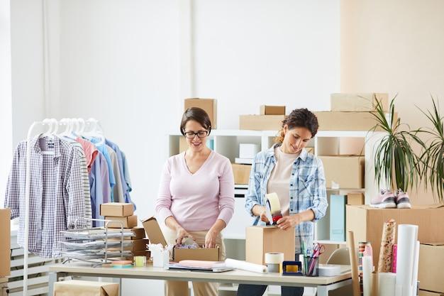 クライアントのために小包を作っている間、机のそばに立っている若い女性の同僚