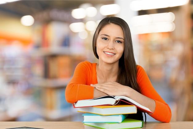 Молодая студентка колледжа и стопка книги на столе на фоне библиотеки