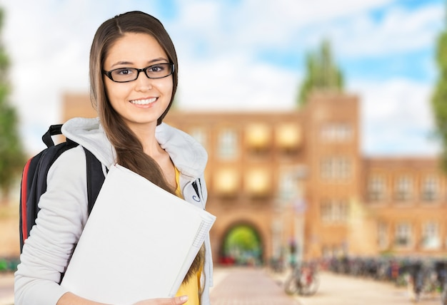 Young female college student  on background