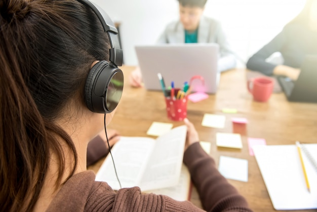 Young female college student wearing headphone listening and reading book