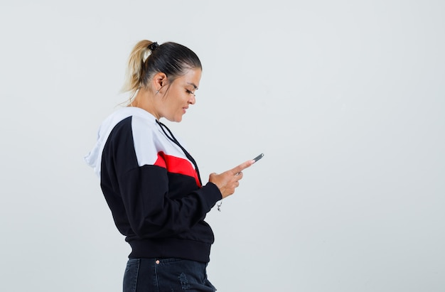 Молодая женщина, сосредоточенная на телефоне в красочной толстовке, выглядит довольной. .