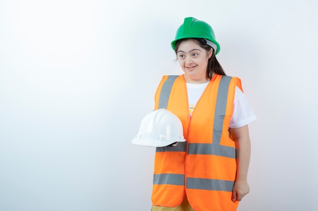 Young female construction worker in hardhat holding helmets over white wall.