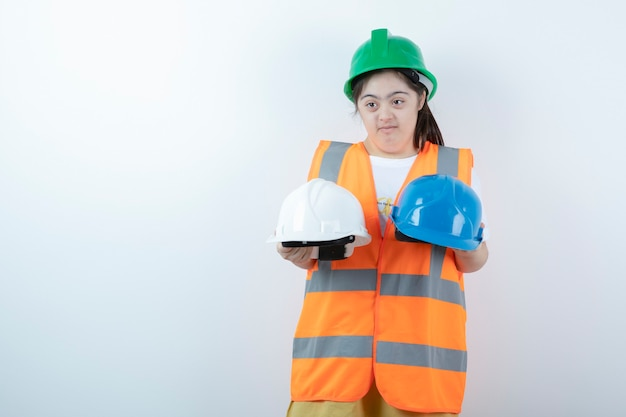 Young female construction worker in hardhat holding helmets over white wall