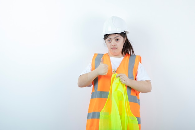 Young female construction worker in hardhat wearing vest over white wall.