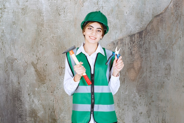 Young female construction worker holding hammer over marble