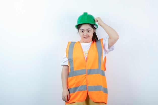 白い壁の上に立っているヘルメットの若い女性の建設労働者