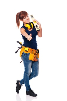 Giovane operaio edile femminile che mostra segno giusto