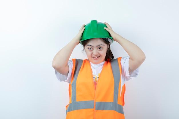 흰 벽에 그녀의 녹색 헬멧을 착용하는 젊은 여성 건설 노동자