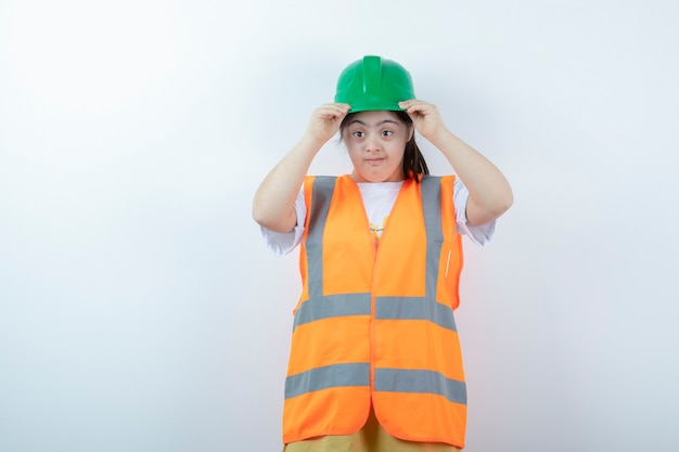 Young female construction worker wearing her green helmet over white wall