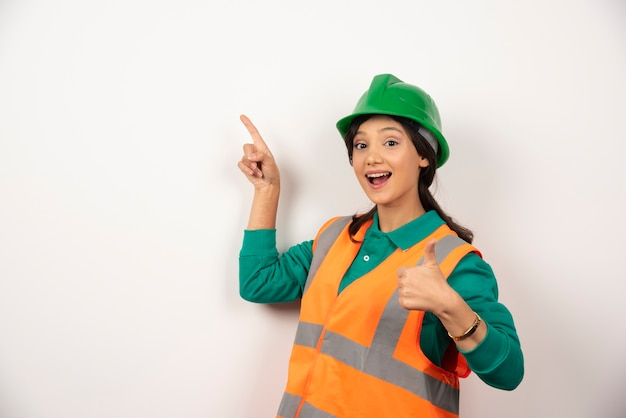 Young female construction worker on white background.