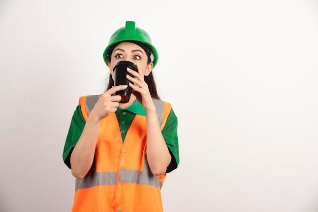 Giovane costruttore femminile che beve dalla tazza e distoglie lo sguardo. foto di alta qualità