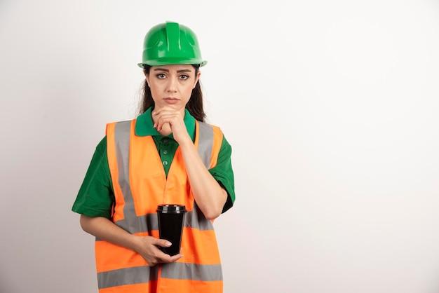 Giovane costruttore femminile che tiene tazza nera. foto di alta qualità