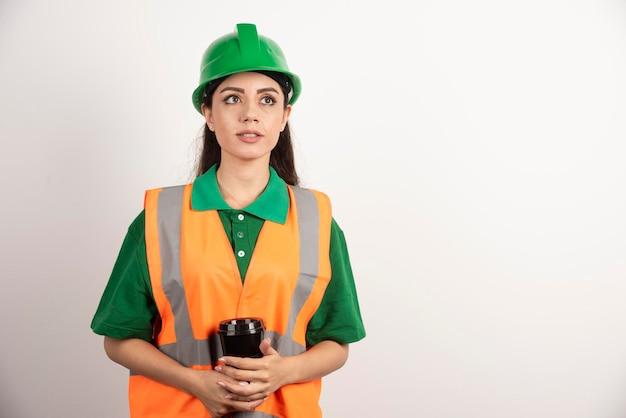 Giovane costruttore femminile che tiene tazza nera e distoglie lo sguardo. foto di alta qualità