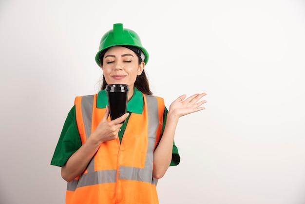 Giovane costruttore femminile che fiuta dalla tazza nera. foto di alta qualità