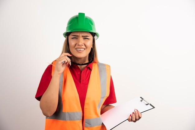 Молодой женский конструктор с изумленными взглядами, держа доску сзажимом для бумаги.