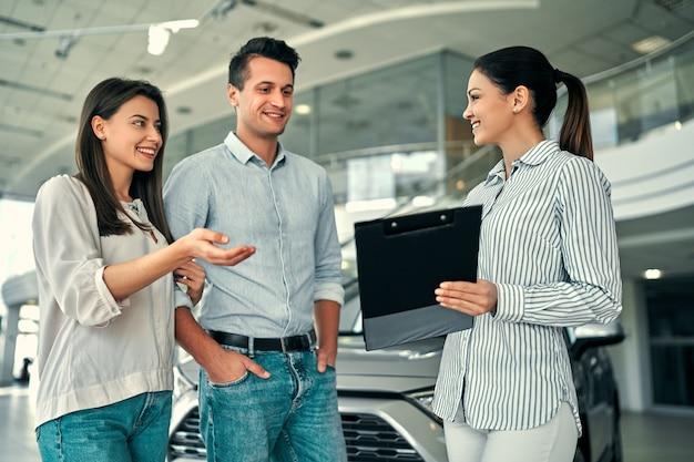 Молодая женщина-консультант и пара покупателей подписывают контракт на новый автомобиль в автосалоне. концепция проката автомобилей.